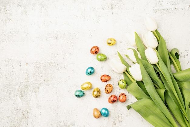 Oster- und frühlingskonzept. draufsicht von weißen tulpen und farbigen ostereiern auf betonhintergrund