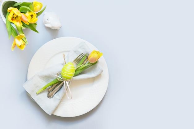 Osterabendessen gedeck mit gelber tulpe auf tabelle. draufsicht