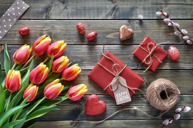 Osterarrangement: rote tulpen, verpackte geschenke, schnur und dekorative herzen auf hölzernem tabke, flach gelegt