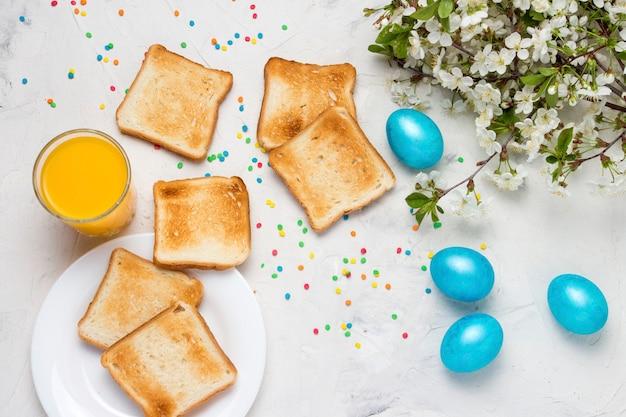 Osterblaue eier, toast und orangensaft auf dem hellen hintergrund. draufsicht.