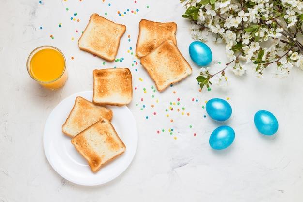 Osterblaue eier, toast und orangensaft auf dem hellen hintergrund.