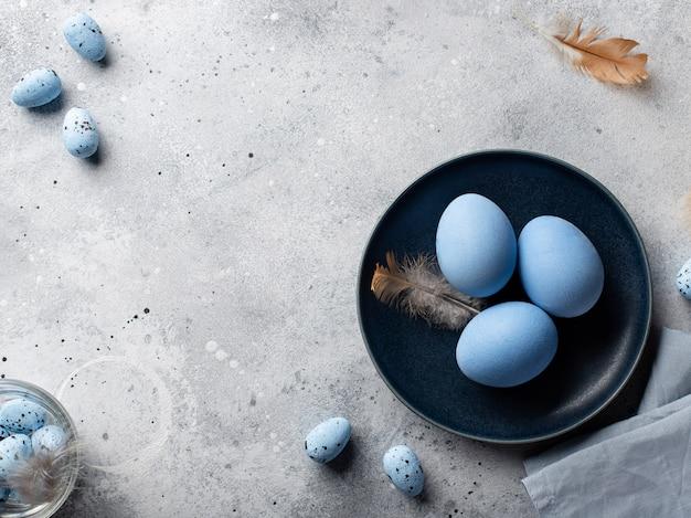 Osterblaue eier und federn in einer dunkelblauen schüssel. frohe ostern! vorbereitung auf den urlaub. grauer betonhintergrund. draufsicht