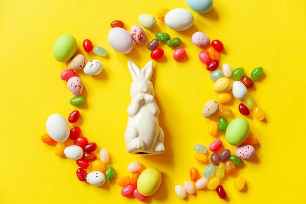 Osterbonbon schokoladeneier hase und jellybean lokalisiert auf gelbem hintergrund
