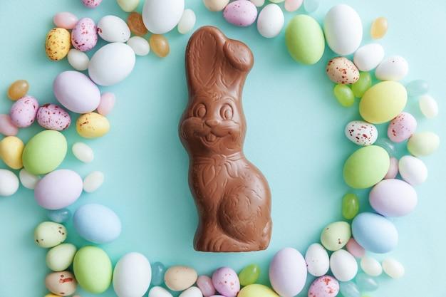 Osterbonbon schokoladeneier hase und jellybean süßigkeiten lokalisiert auf blauem tisch