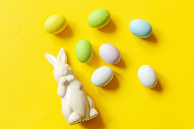 Osterbonbon schokoladeneier süßigkeiten und häschenspielzeug lokalisiert auf trendigem gelbem tisch