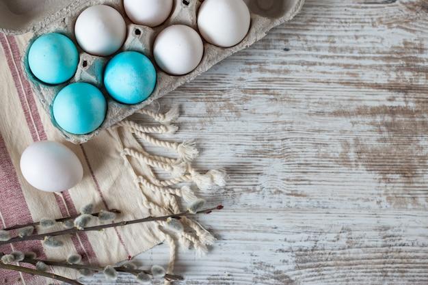 Osterdekoration mit eiern auf einem weißen holztisch. von oben betrachten