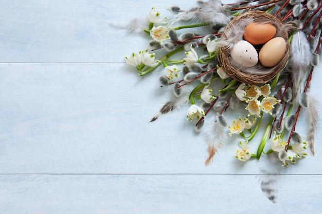 Osterdekoration ostereier im nest und weidenkätzchen und schneeglöckchen.