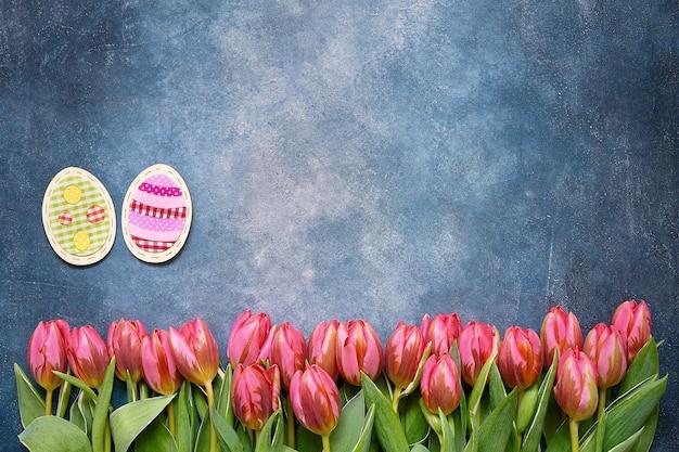 Osterdekoration und rosa tulpen auf blauem tisch. osterkonzept. speicherplatz kopieren, draufsicht