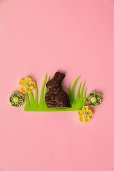 Osterdekorationen und süßigkeiten auf rosa