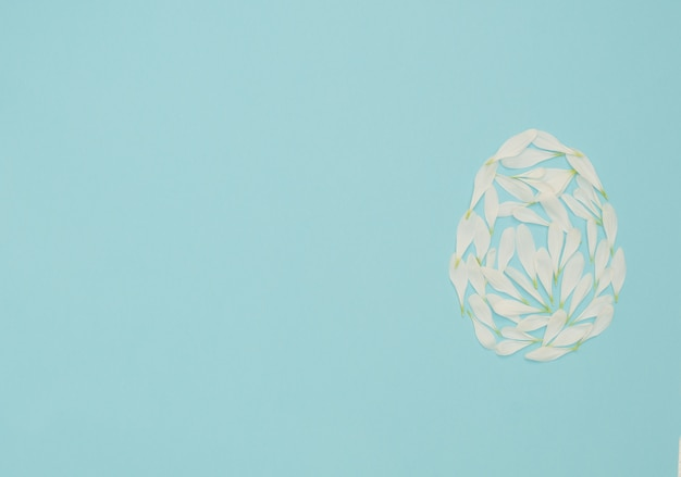 Osterei aus weißen blütenblättern auf blau