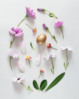 Osterei-layout aus bunten blumen, grünen blättern und goldenem ei