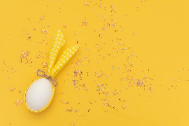 Osterei mit den hasenohren auf gelbem hintergrund. minimales ostern-konzept
