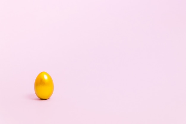 Osterei verziert mit goldfarbe auf einem rosa hintergrund. konzept für ostern, frühling. selektiver fokus. speicherplatz kopieren.