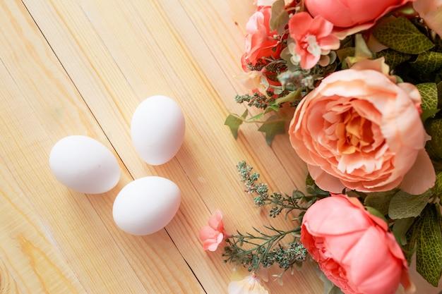 Ostereier auf weißem holztisch. blumen und süßigkeiten herum.