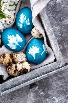 Ostereier aus natürlichem farbstoff bemalt und mit pflanzenblättern verziert
