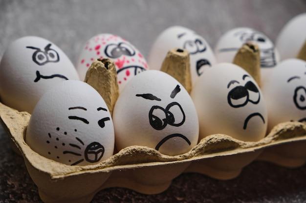 Ostereier eier in masken. tablett der weißen eier mit gezeichneten lustigen gesichtern, die medizinische masken an den osterferien während der coronavirus-epidemie schließen, schließen