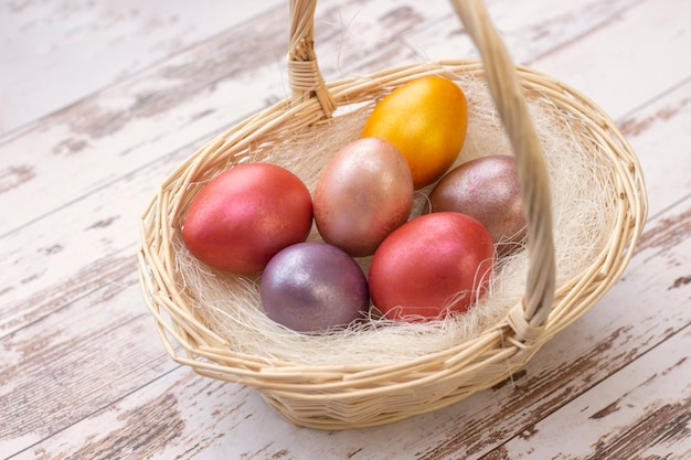 Ostereier. farbige eier in einem korb an ostern. auf hellem hintergrund, holzuntergrund.