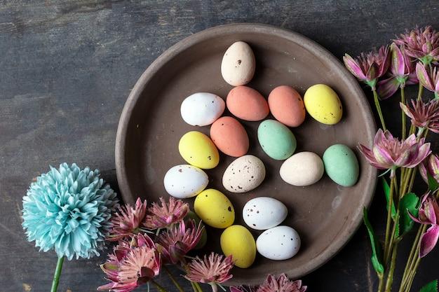 Ostereier gemalt in den pastellfarben auf einer weinlesehintergrundhintergrundbeschaffenheit, betonblickplatte umgeben mit verschiedenen frühlingsblumen in den modernen farben. retro design draufsicht