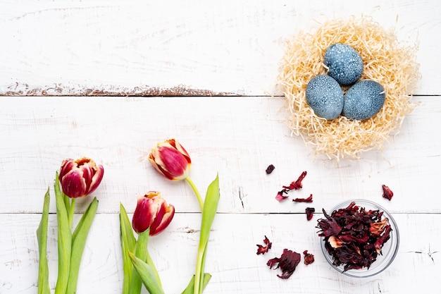 Ostereier, gemalt mit natürlichen farbstoffen, hibiskusblüten, karkade-tee, auf einem weißen gealterten holztisch, rote frühlingsblumen-tulpen.