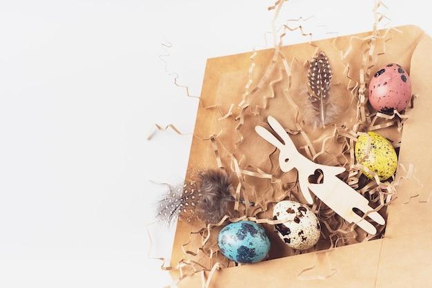 Ostereier, hasen, federn, heu in einem handwerklichen umschlag auf weißem hintergrund. feiertagsnachricht frohe ostern, korrespondenzkonzept. flache lage, ansicht von oben. osterkarte.