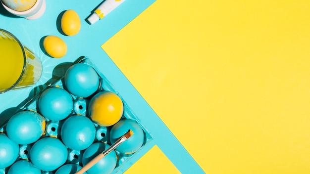 Ostereier im gestell mit pinsel und papier auf blauer tabelle
