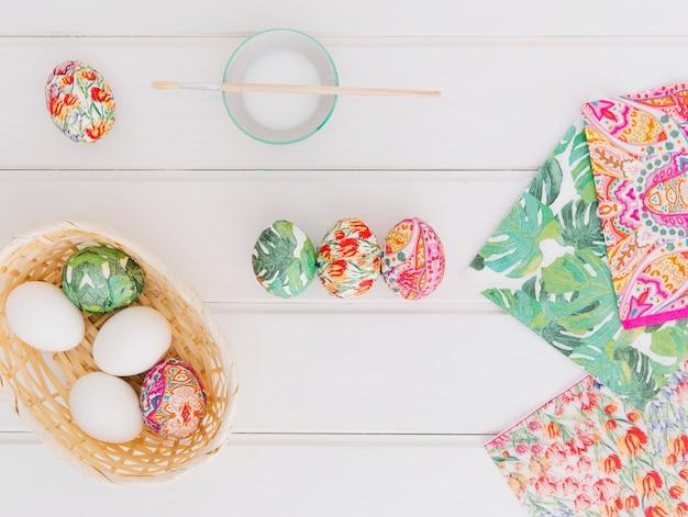 Ostereier im korb in der nähe von servietten und pinsel auf cup mit farbstoff flüssigkeit