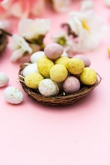 Ostereier im nest auf rosa hintergrund. frühlingsgrußkarte mit kopienraum.