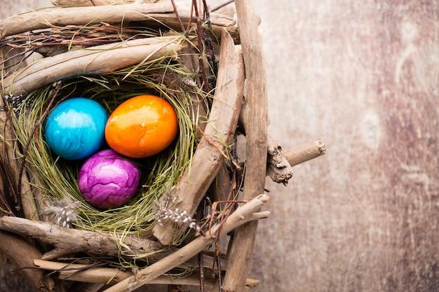 Ostereier im nest auf rustikalem hölzernem hintergrund