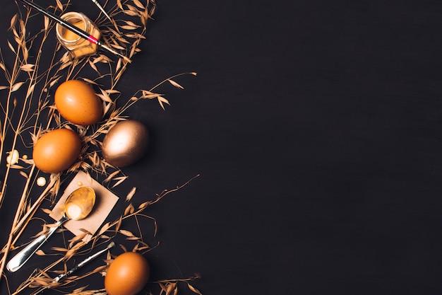 Ostereier in der nähe von löffel auf papier und pinsel auf farbstoff können zwischen trockenem gras