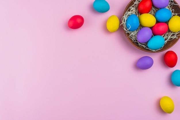 Ostereier in der schüssel auf rosafarbener tabelle