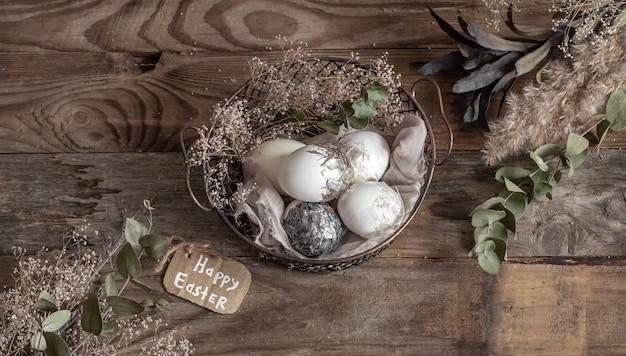 Ostereier in einem dekorativen korb mit getrockneten blumen auf einem holztisch. frohe ostern konzept.