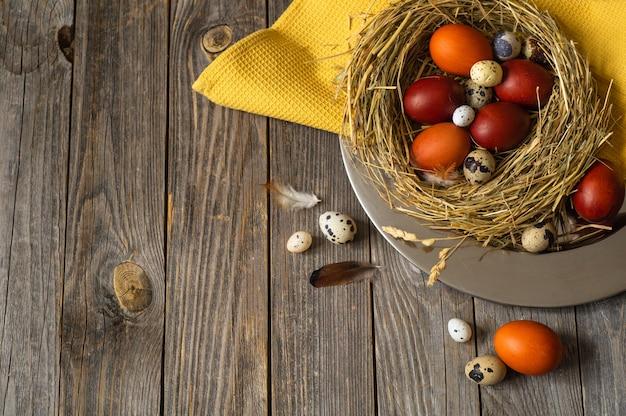 Ostereier in einem nest auf einer metallplatte auf einem holztisch. frohe ostern konzept