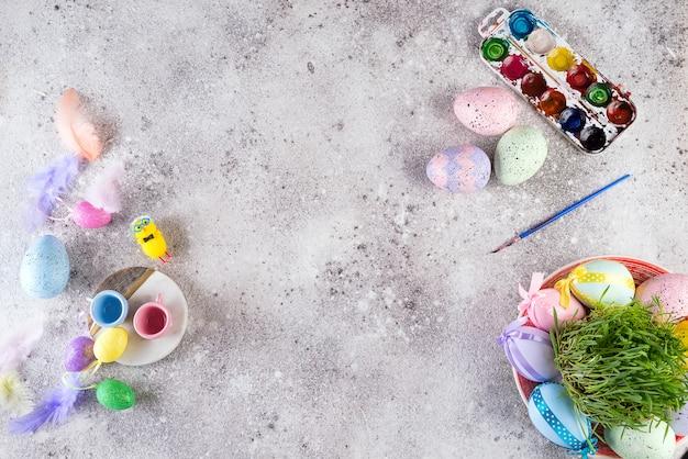 Ostereier in einem nest aus gras, hausgemachte glasierte kekse und farben zum malen von eiern und gras