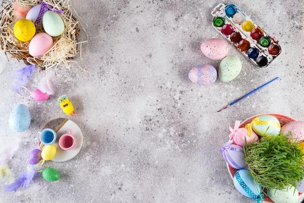 Ostereier in einem nest aus gras, hausgemachte kekse und farben zum bemalen von eiern