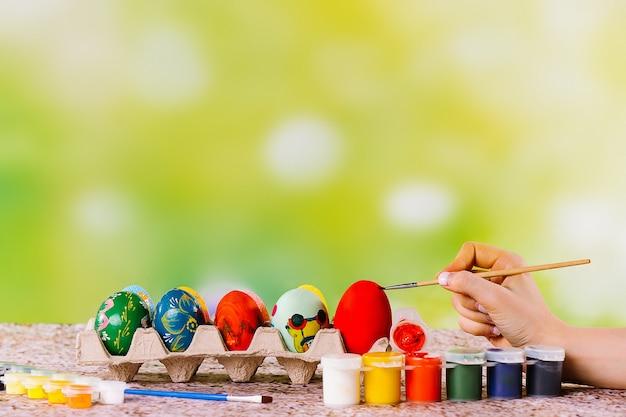 Ostereier in einem pappnestständer werden von weiblicher hand mit hellen acril-farben auf einem grün gemalt