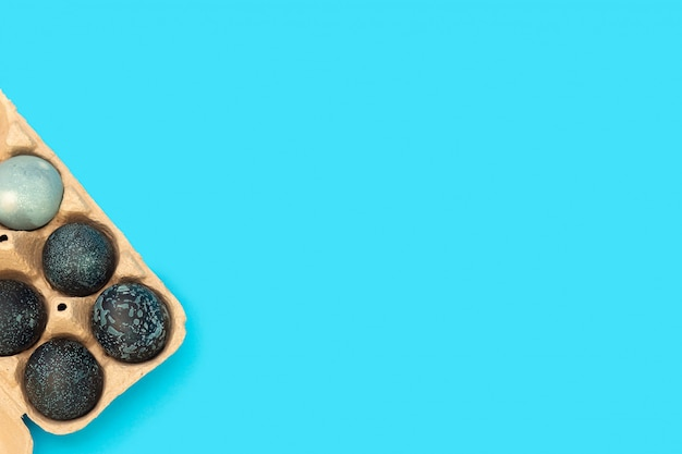 Ostereier in einer in raumfarbe gemalten eierbox liegen auf einem blauen hintergrund mit raum für text