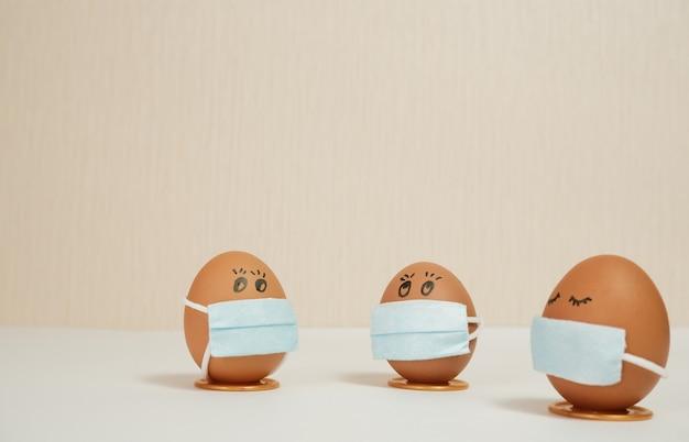 Ostereier in einer schützenden medizinmaske auf pfirsichhintergrund