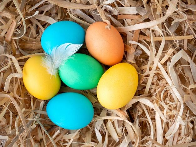 Ostereier in verschiedenen farben im nest. nahansicht. frohe ostern