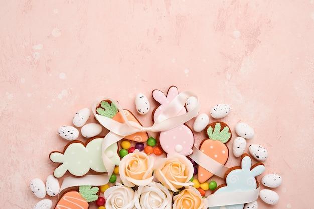 Ostereier, keks und bunte süßigkeit gemacht in form des kreiskranzes auf rosa hintergrund