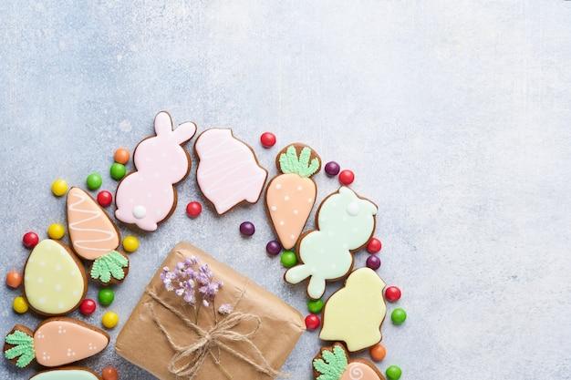 Ostereier, kekse und bunte süßigkeiten in form eines kreiskranzes auf grauem hintergrund. minimales urlaubskonzept mit kopienraum für text. flaches lay-muster.