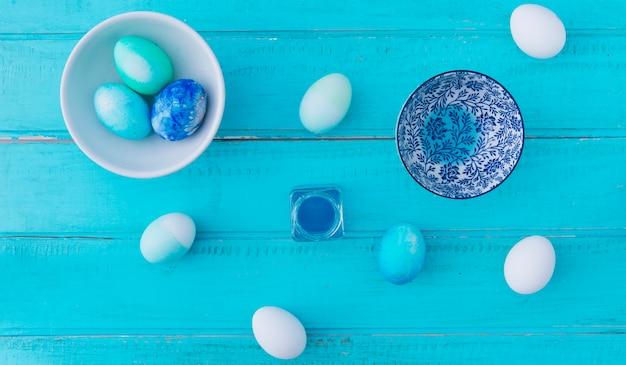 Ostereier können in der nähe mit farbstoff, schüssel und teller an bord