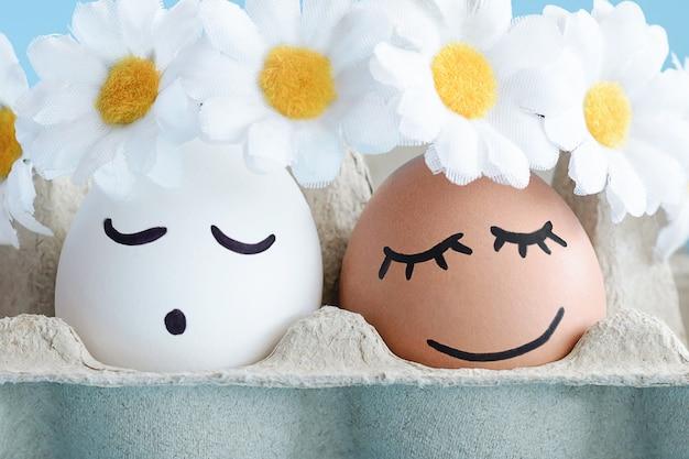Ostereier mit gezeichneten niedlichen lächelnden gesichtern in den blumenkränzen im weichen licht