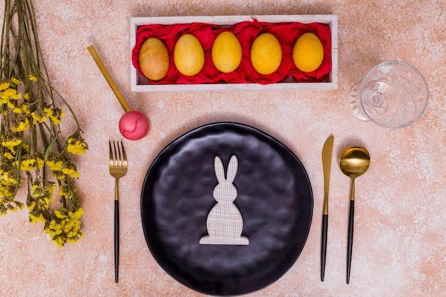 Ostereier mit hölzernem kaninchen auf platte