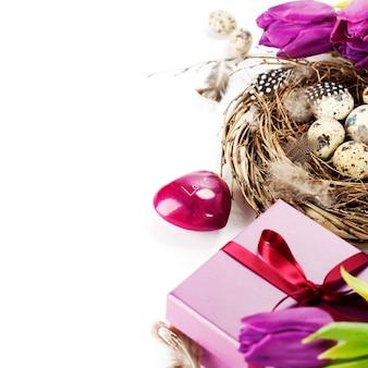 Ostereier mit lila tulpenblumen und geschenken