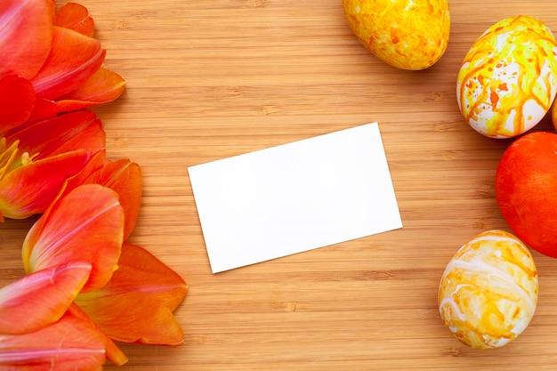 Ostereier mit tulpen auf hölzernem brett, ostern-feiertagskonzept. exemplar für text