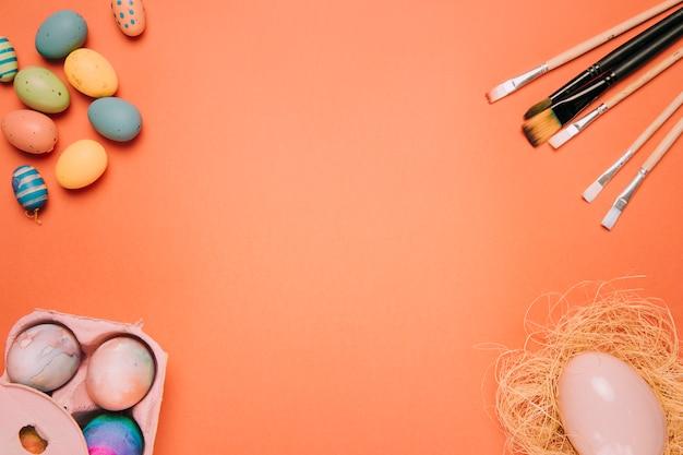 Ostereier; pinsel; eiernest an der ecke des orangefarbenen hintergrunds