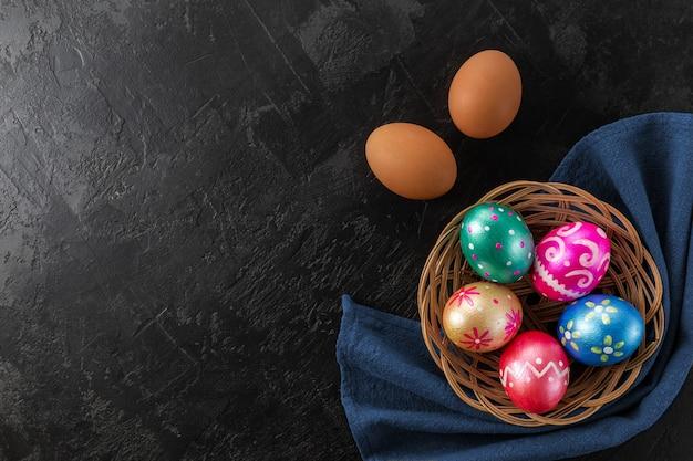 Ostereier trendig gefärbt tiefblau, grün, orange, magenta und golden im korb verziert