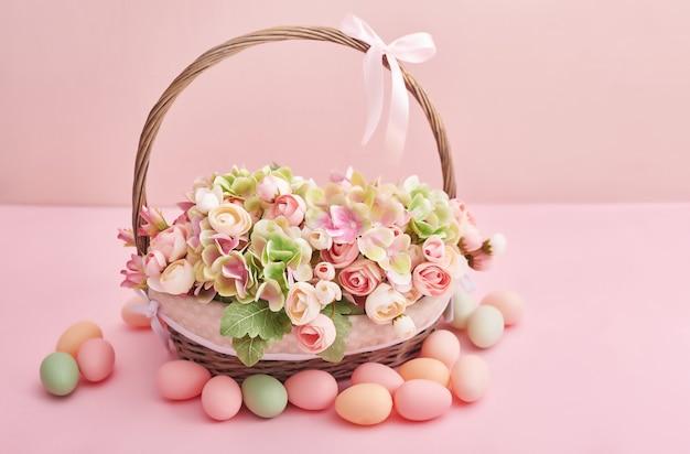 Ostereier und blumen. osterkorb mit blumen und eiern auf rosa hintergrund