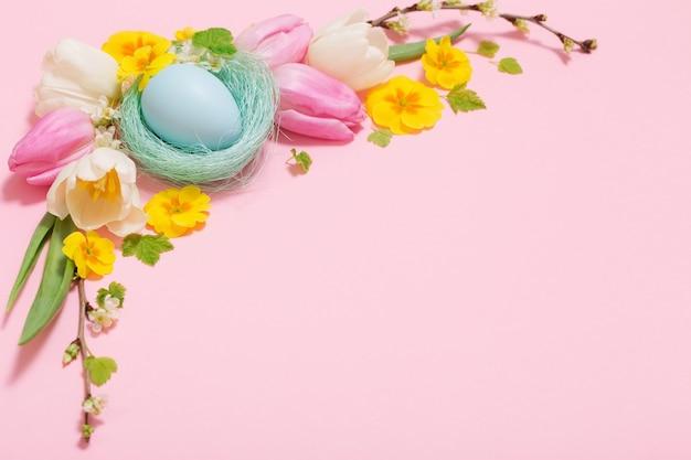 Ostereier und frühlingsblumen auf rosa hintergrund