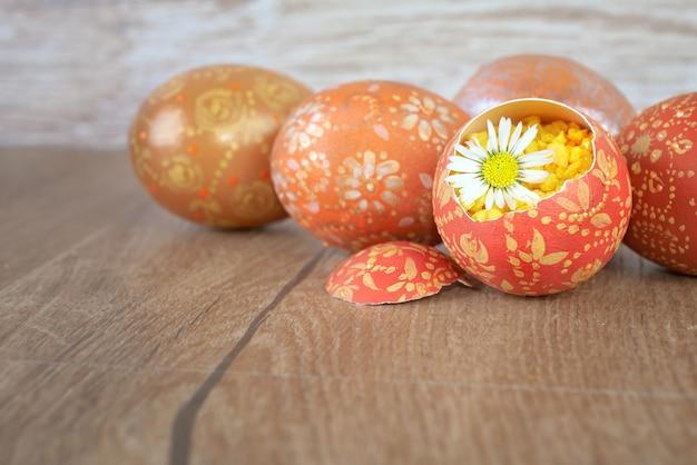 Ostereier und gänseblümchenblume auf holztisch